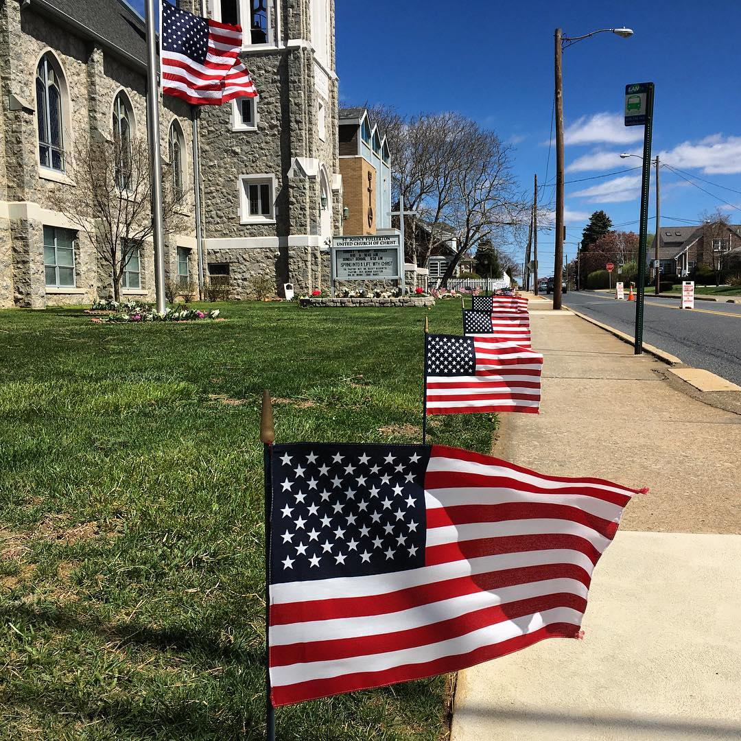 Flags line the sidewalk for the funeral service of longtime Whitehall, Pa. Fire Chief Robert Benner.