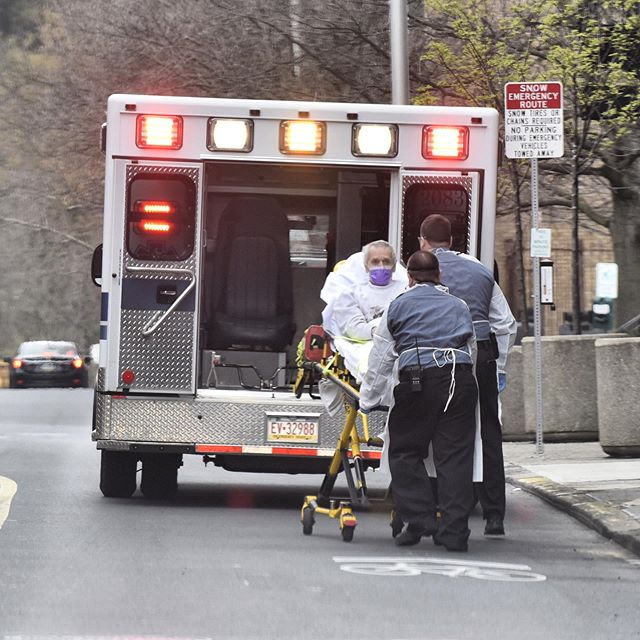EMS crews use special personal protective equipment while picking up a patient on Monday.